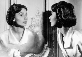Actress Audrey Hepburn looking at her reflection in the mirror January 16