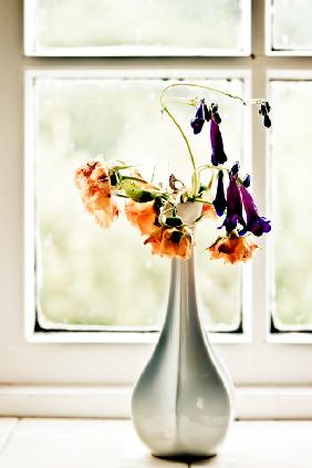 Vase with orange and violet flowers